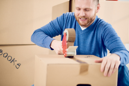 moving box: Young Caucasian man using duct tape for packing stuff in box