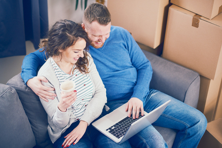 moving box: Couple using laptop in new apartment while sitting on sofa