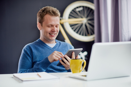 Businessman sitting and using tablet device at home office Stock Photo