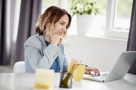 Businesswoman using laptop and drinking coffee while sitting at modern home office Stock Photo