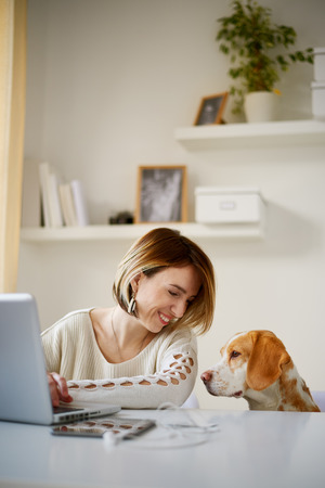 Caucasian woman working at home office while her dog watching her/ businesswoman in thirties concept