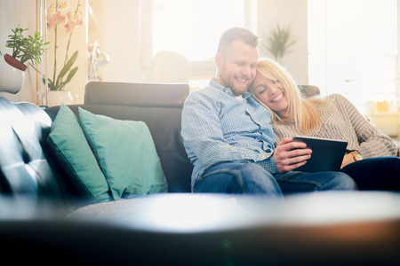 connection connections: Caucasian couple using tablet while sitting on sofa in living room