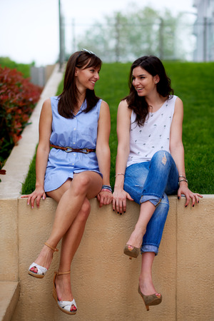 Two girls chatting and sitting on wall with legs crossed