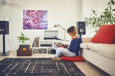 Vrouw luisteren naar vinyl thuis Stockfoto
