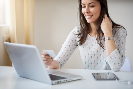 Woman using laptop and credit card for on-line shopping at home office