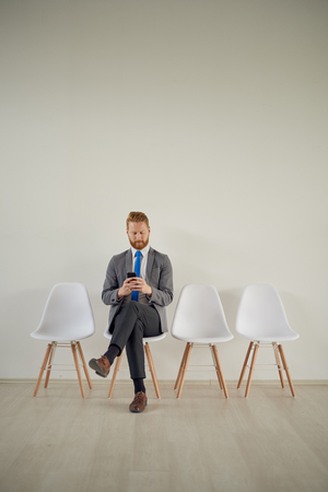 telephone interview: Businessman sitting in modern office while sitting in waiting room Stock Photo
