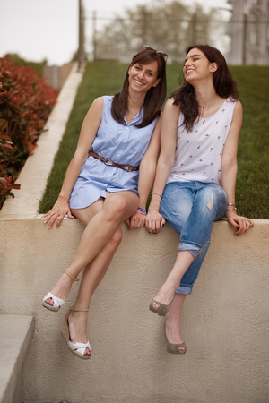 Two girls sitting in the wall Stock Photo