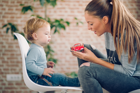 Mom playing with her son in cosy living room Stock Photo