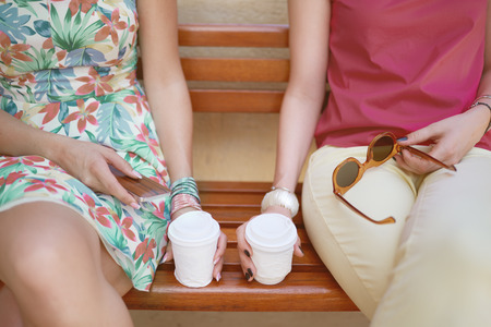 Close up of hands holding coffee to go. Two girls sitting on the bench