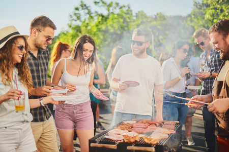 Group of people standing around grill, chatting, drinking and eating. Stock Photo