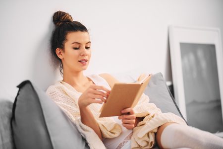 Girl reading book while sitting in the bed at the morning