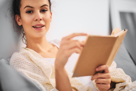 Girl reading book while sitting on the bed in the morning Stock Photo