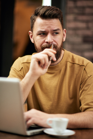 Man using laptop and smart phone while sitting in cafe. New technologies concept Stock Photo