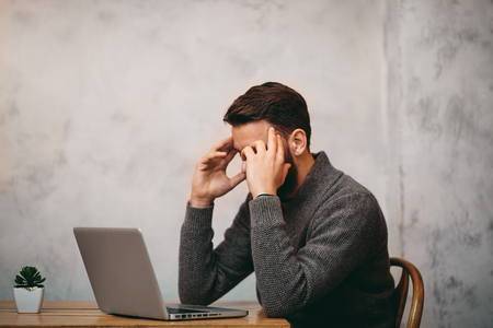 Man having headache while sitting in cafe. Laptop in front of him  and hands on head