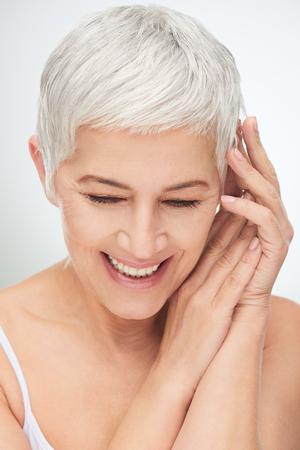 Portret van mooie hogere vrouw voor witte achtergrond. Stockfoto