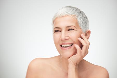 Porträt der schönen älteren Frau vor weißem Hintergrund. Standard-Bild