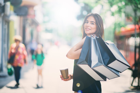 Portrait of woman holding paper bags and coffee on the street after shoping while using smart phone. Stock Photo