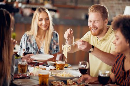 Przyjaciele jedzący obiad w restauracji. Wieloetniczna grupa.