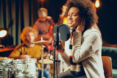 Mixed race woman singing. In background band playing instruments. Home studio interior. Stock Photo