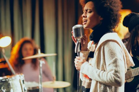 Close up of mixed race woman singing. In background band playing instruments. Home studio interior.