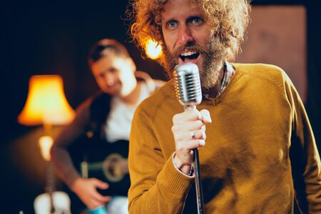 Close up of young Caucasian man with curly hair holding microphone and singing. Home studio interior.
