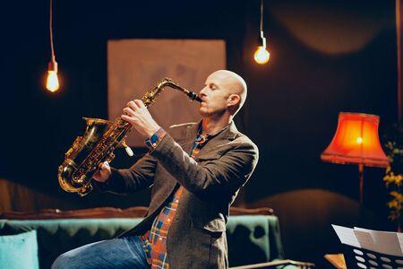 Portrait de saxophoniste chauve jouant de son instrument en home studio. Banque d'images