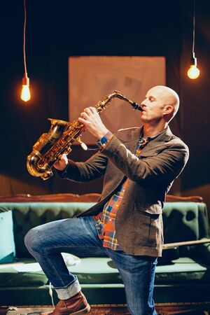 Portrait of bald saxophonist playing his instrument in home studio. Imagens