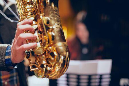 Close up og man playing saxophone. Home studio interior.