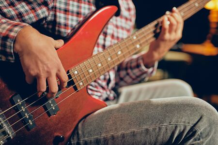 Close up of young man playing bass guitar. Home studio interior. Imagens