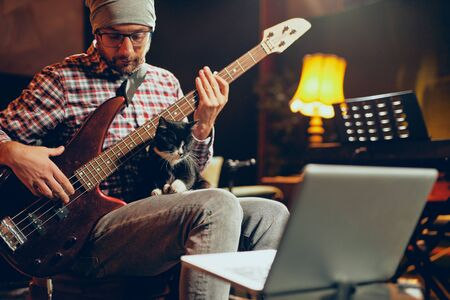 Young Caucasian man with hat on head playing bass guitar while sitting in home studio. Imagens