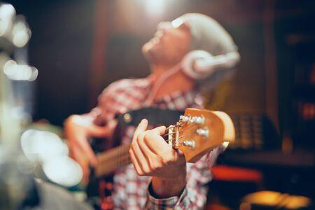 Close up of young man playing bass guitar. Home studio interior. 스톡 콘텐츠