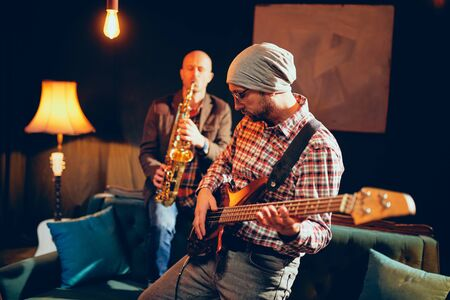 Two Caucasian great musicians playing bass guitar and saxophone in home studio.