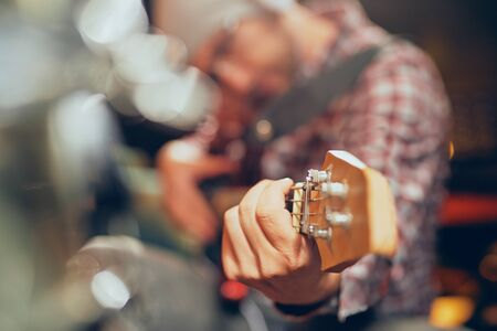 Close up of young musician playing bass guitar with earphones on ears. Selective focus on hand.