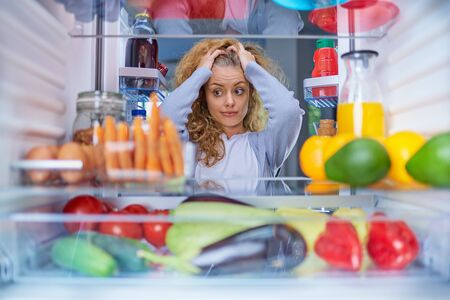 Confused hungry woman holding hands on head while standing in front of opened fridge full of groceries.
