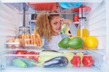 Woman standing in front of opened fridge and holding up to her nose because of bad smell. Picture taken from the inside of fridge full of groceries.