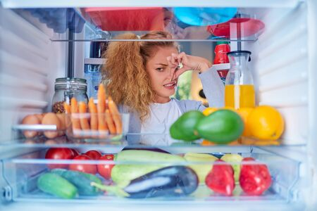 Womann standing in front of opened fridge and holding up to her nose because of bad smell. Picture taken from the inside of fridge full of groceries.