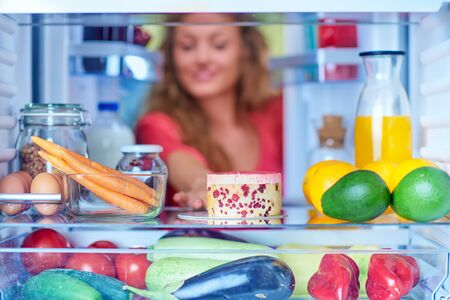 Woman taking gateau form fridge full of groceries. Unhealthy eating concept. Picture taken from the inside of fridge. Zdjęcie Seryjne