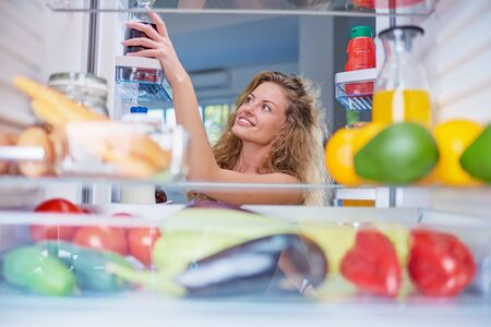 Woman taking food from fridge full of groceries. Picture taken from the inside of fridge. Stockfoto