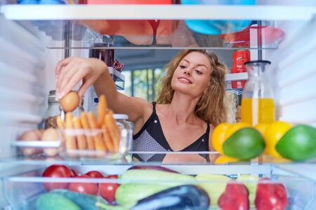 Young Caucasian woman taking egg from fridge to make a breakfast. Picture taken from inside of fridge.