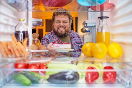 Man taking cheesecake from fridge. Picture taken form inside of fridge.