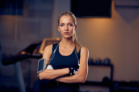 Woman standing in a gym with arms crossed. Healthy lifestyle concept. 免版税图像