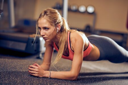Woman doing planks on gym floor. Healthy lifestyle concept. Imagens