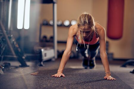 Sporty woman doing push-ups on the floor. In background exercise equipment. Gym interior.