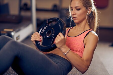 Close up of woman doing exercises with weight plate while sitting on the gym floor.  Side view, healthy lifestyle concept.