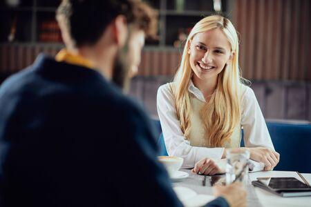 Glimlachende blanke blonde zakenvrouw gekleed smart casual in gesprek met haar mannelijke collega over project terwijl ze in de coffeeshop zit. Stockfoto