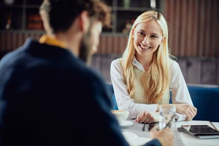 Smiling Caucasian blonde businesswoman dressed smart casual discussing with her male colleague about project while sitting in coffe shop. Foto de archivo