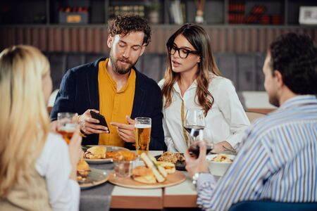 Young attractive Caucasian couple sitting in restaurant and looking at smart phone. In foreground their friends sitting adn drinking.