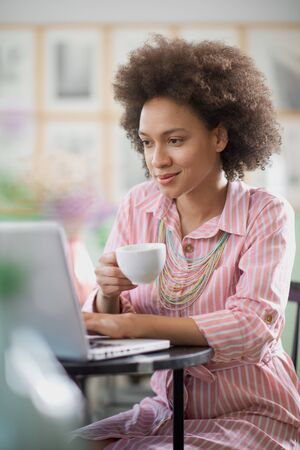 Charming mixed race woman in striped pink dress aitting in coffee shop, drinking coffee and using laptop. Stock Photo