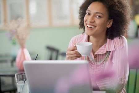 Charming mixed race woman in striped pink dress sitting in coffee shop, drinking coffee and using laptop. Фото со стока