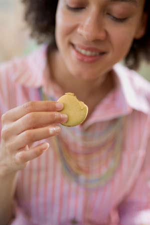 Close up of beautiful smiling mixed race woman in pink striped dress sitting in confectionery and eating cookie.